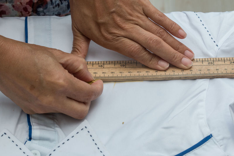 Midsection of tailor measuring textile