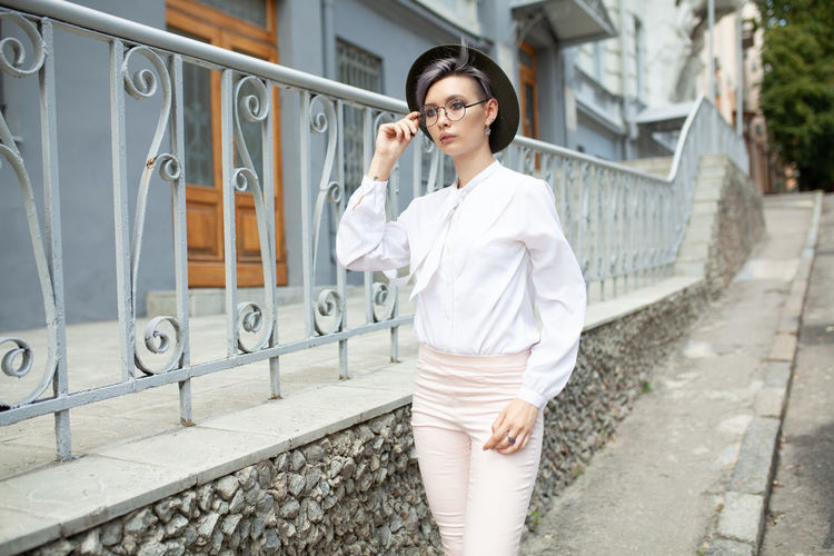 Woman Wearing Eyeglasses And Hat While Walking In City