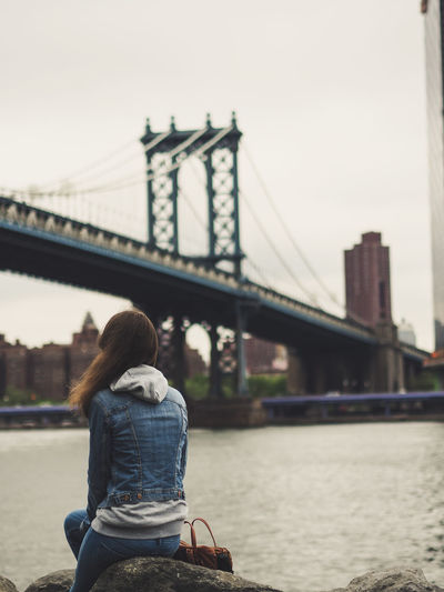 Rear view of woman sitting by manhattan bridge in city