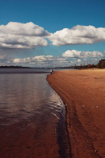 Distant view of person walking on shore against sky