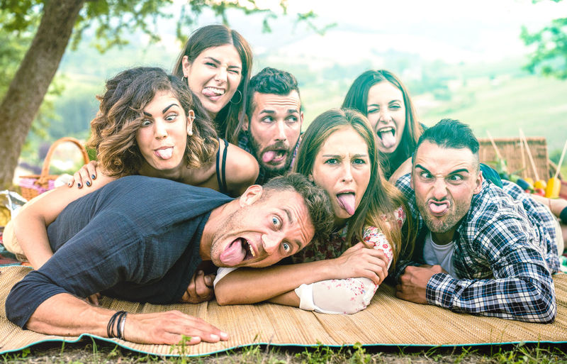 Millenial friends taking selfie with funny faces at pic nic barbecue - Happy youth friendship concept with millennial young people having fun together with tongue out - Bright green azure filter Backyard Barbecue BBQ Best  Boho Camping Campus Cheerful College Community Concept Country Countryside Faces Fancy Friends Friendship Fun Garden Gen Generation Grass Group Happy Having Hipster Influencer Life Lifestyle Meadow Millenials Millennials Moment Nature Park Party People Picnic Relax Selfie Spring Summer Teenagers  Tongue Travel Vacation Weekend Young Youth Z