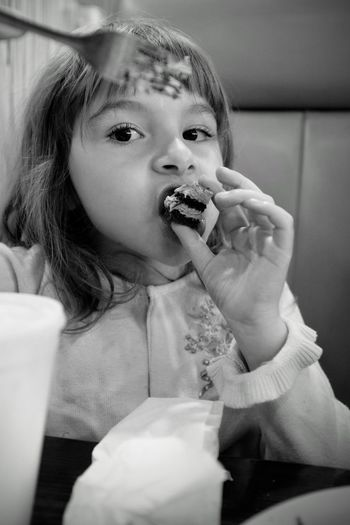 Portrait of cute girl eating cake slice at restaurant