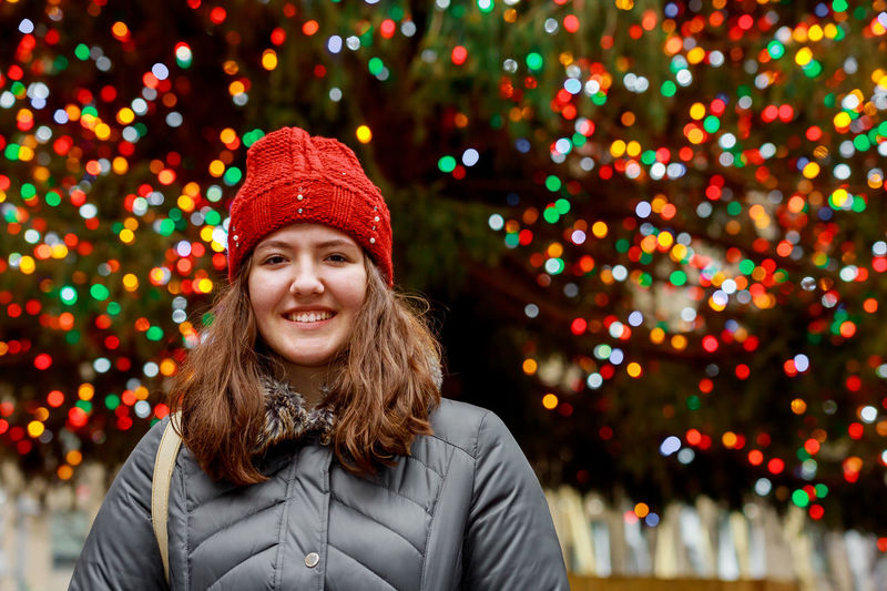 Portrait of smiling girl wearing hat against illuminated lights