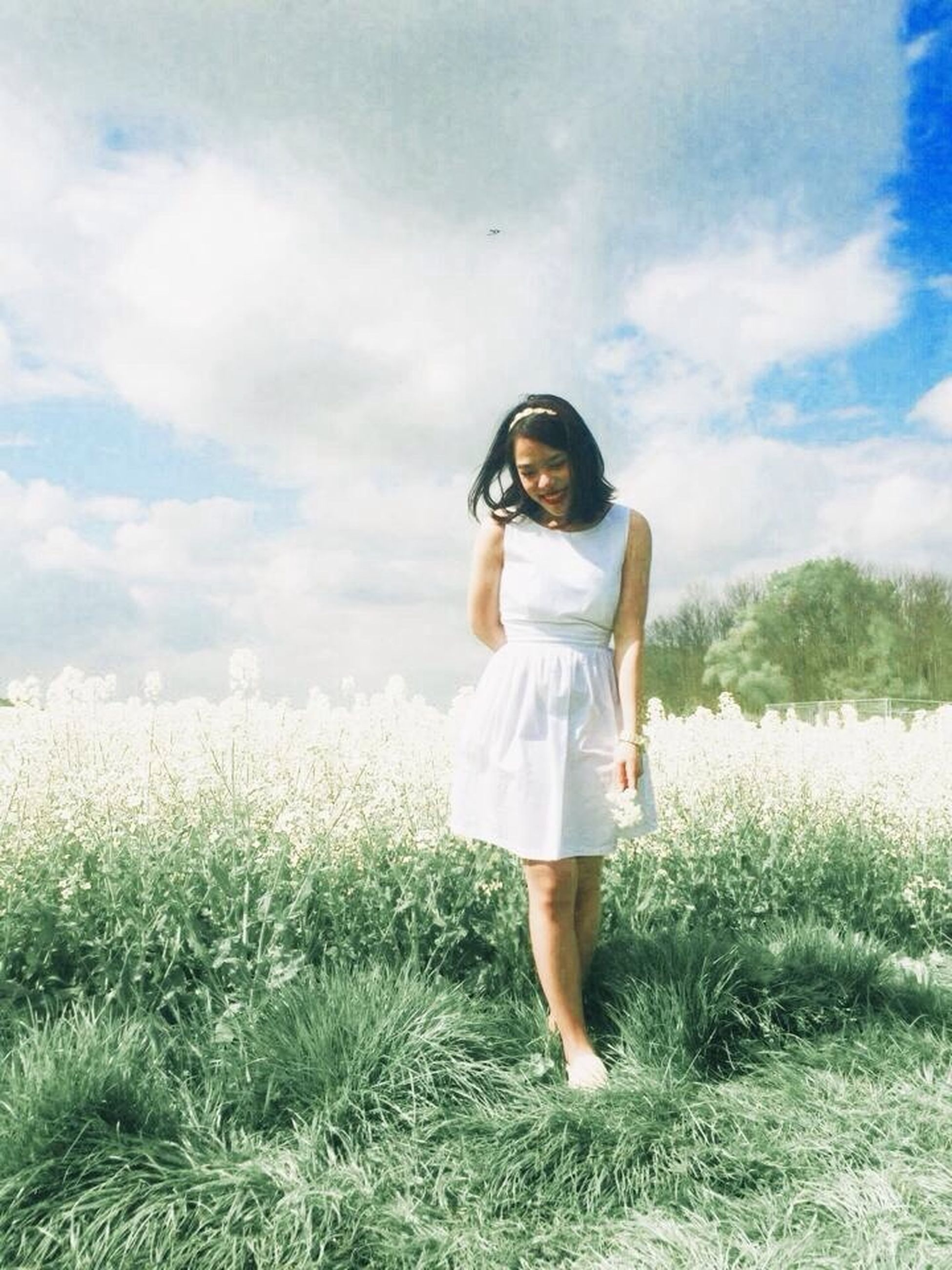 grass, casual clothing, lifestyles, full length, leisure activity, sky, field, person, standing, young adult, young women, plant, growth, nature, three quarter length, front view, grassy, cloud - sky