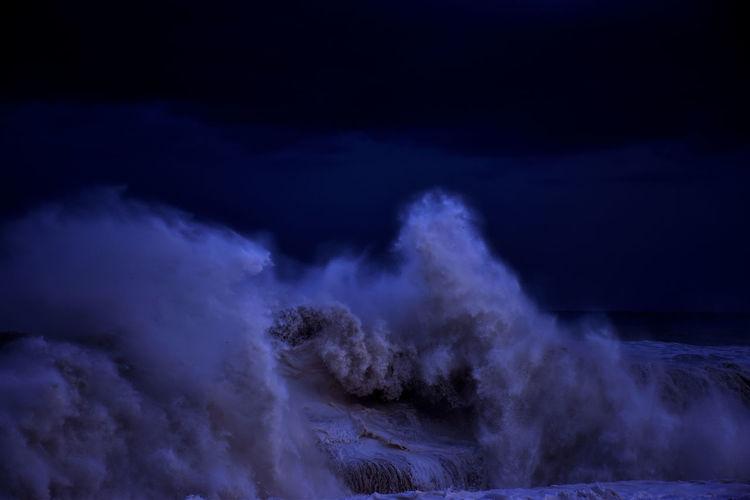 Wave splashing in sea against sky at night