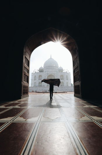 Silhouette person standing against taj mahal