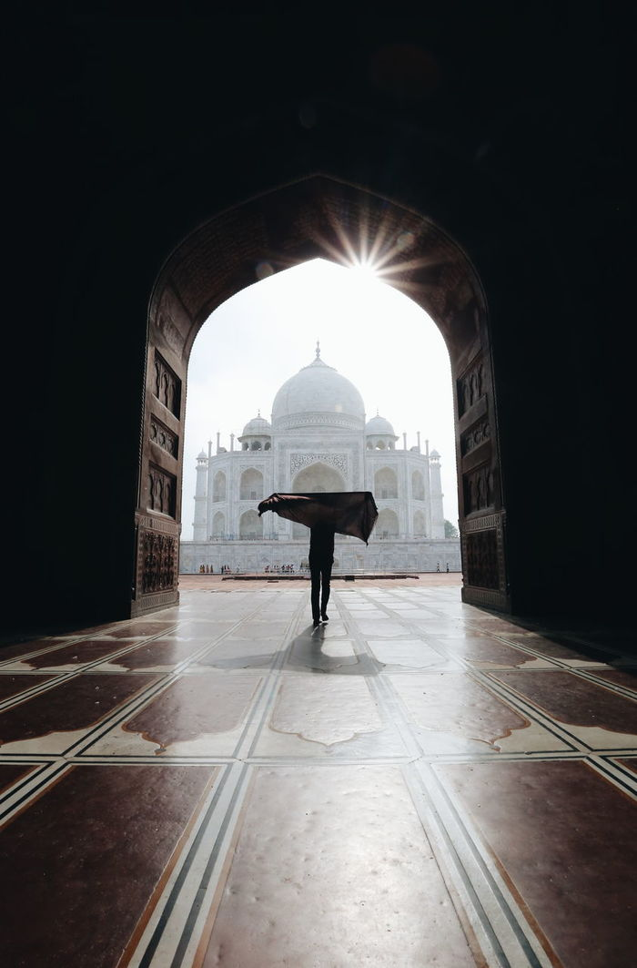 Silhouette person standing against taj mahal