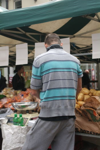 Rear view of man standing at market stall in city