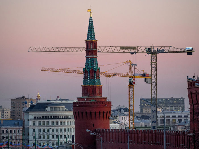 Red square by cranes and buildings against clear sky during sunset