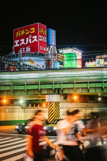 Blurred motion of people on illuminated city street at night