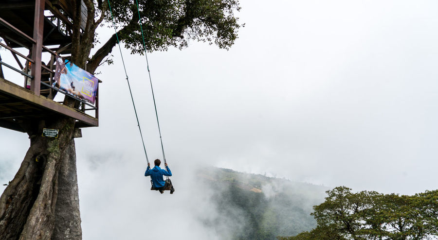 The swing at the end of the world BañosEcuador Travel Adventure Day Ecuador Men Nature One Person Outdoors People Real People Sky Swing Travel Destinations Tree Treeswing