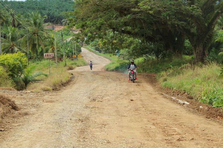 Rear view of man riding motorcycle on dirt road