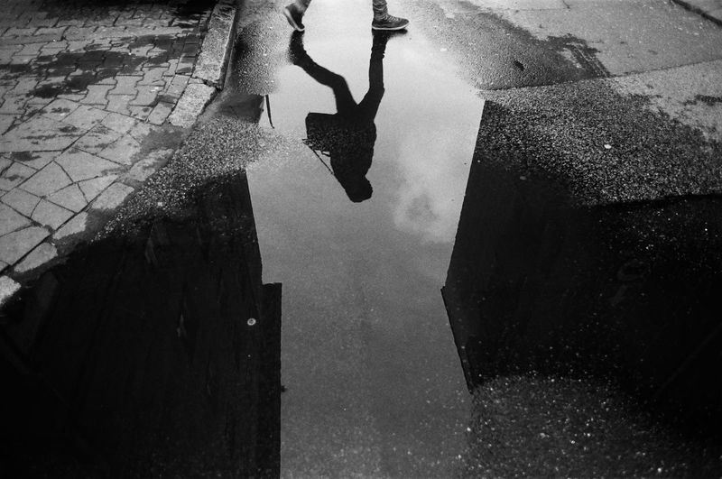 ANALOG: Ilford FP4 125 The Week on EyeEm Capture The Moment Monochrome Film Photography Analogue Photography Street Photography Light And Shadow Black And White Architecture Real People One Person Built Structure City Leisure Activity Lifestyles Human Body Part High Angle View Day Low Section Body Part Puddle Human Leg Building Exterior Men Nature Unrecognizable Person Outdoors Human Limb The Art Of Street Photography