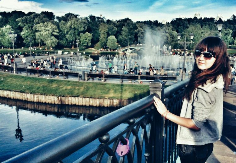 Young woman standing on footbridge over river at tsaritsyno park