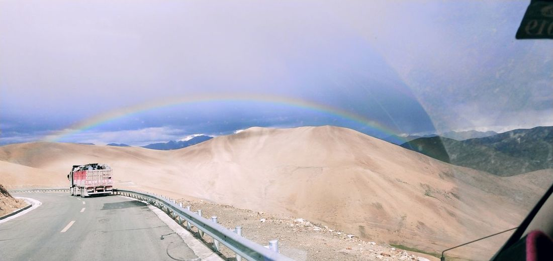 Scenic view of road against rainbow in sky