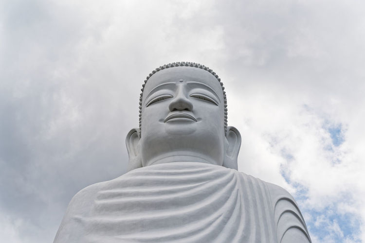 Low angle view of buddha lowtue against against sky