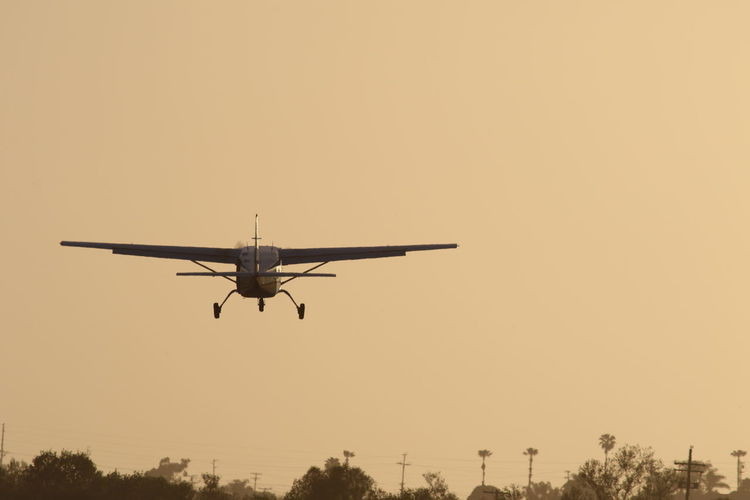 Low Angle View Of Airplane Against Clear Sky During Sunset