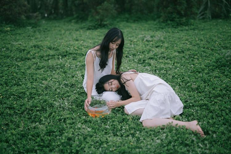Friends relaxing on field