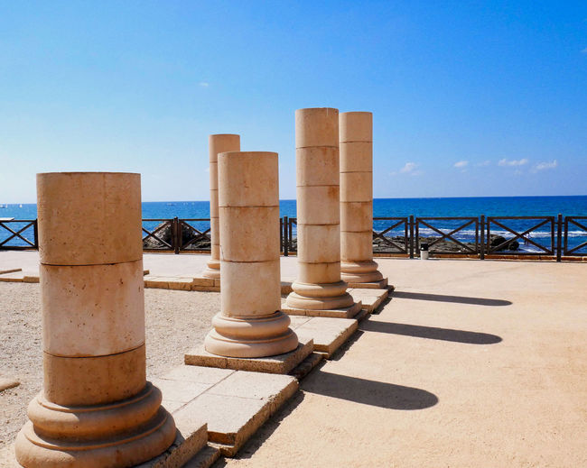 Columns in sea against clear blue sky