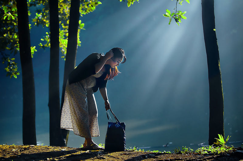 Woman with bag standing amidst trees