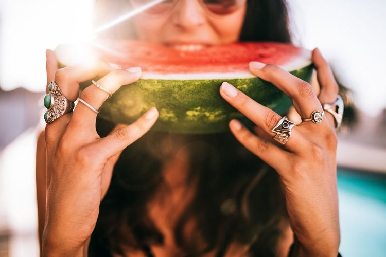 Midsection of woman eating watermelon