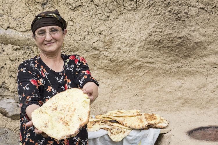 Portrait Of Smiling Woman Holding Bread
