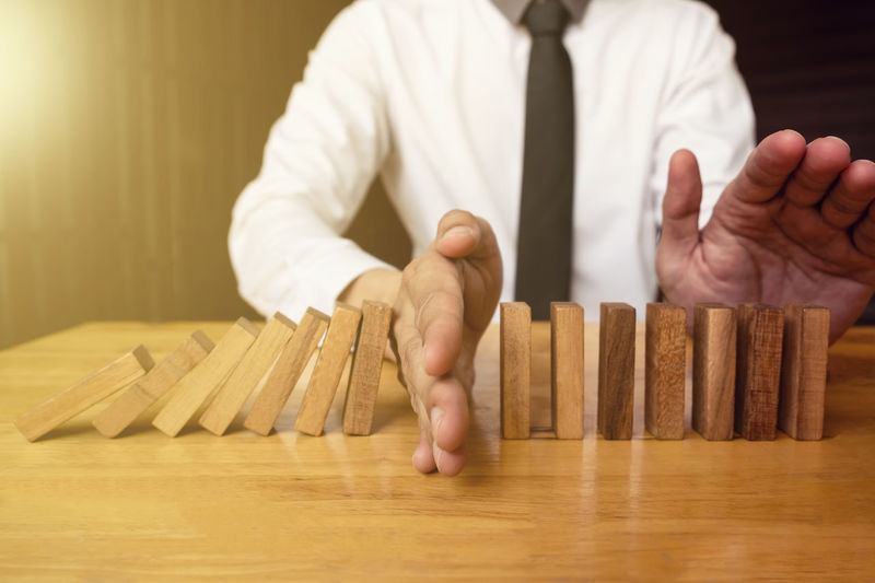 Business Domino RISK Casual Clothing Close-up Continuous Finance Focus On Foreground Front View Hand Holding Human Body Part Human Hand Indoors  Men Midsection Occupation One Person Real People Sitting Standing Stop Table Wood - Material Wooden Block
