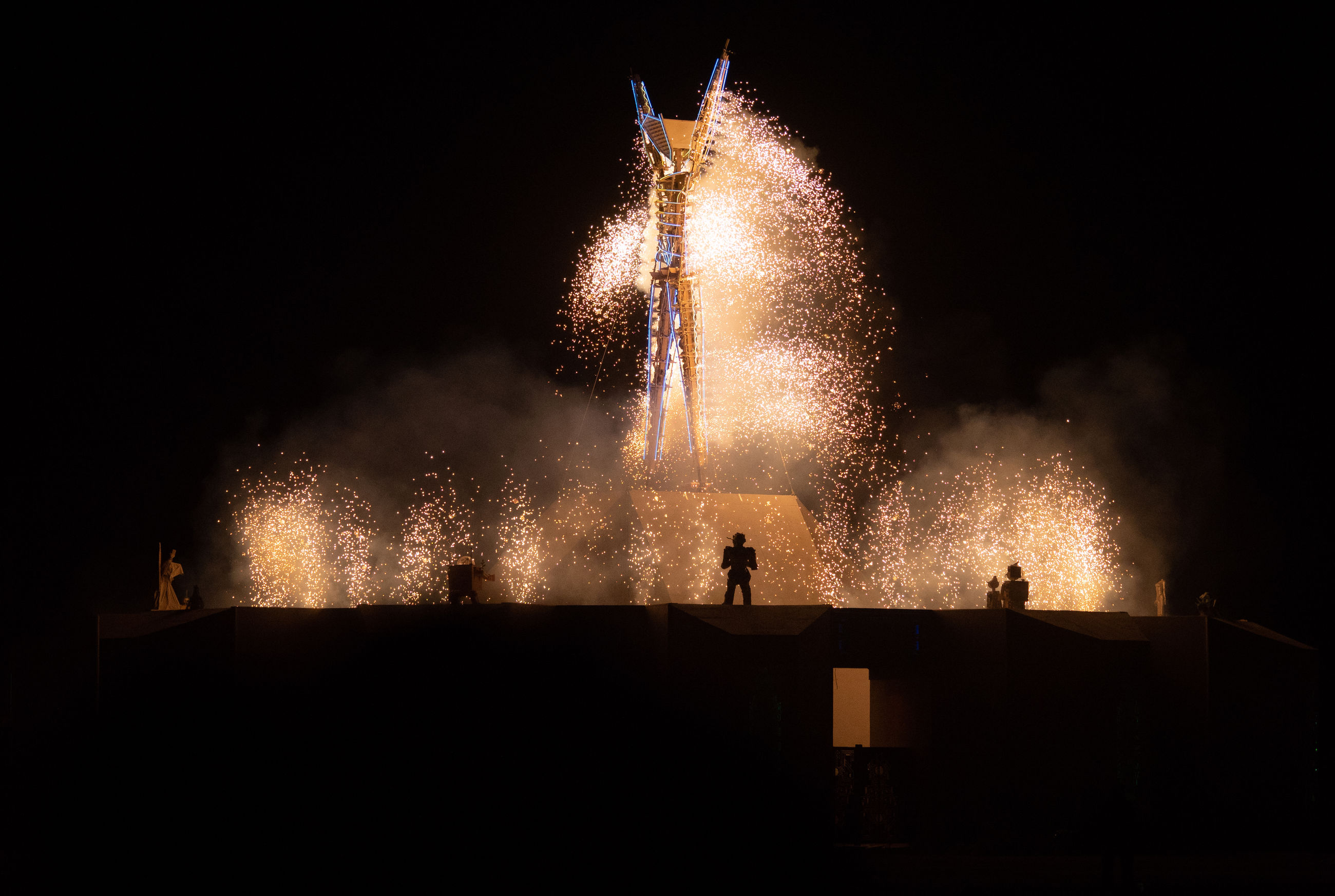 night, motion, arts culture and entertainment, firework, firework display, illuminated, exploding, firework - man made object, glowing, smoke - physical structure, long exposure, celebration, event, nature, group of people, real people, silhouette, architecture, outdoors, sky, sparks