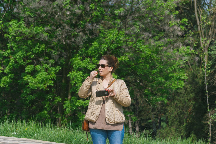 Young Woman Holding Mobile Phone While Standing In Forest