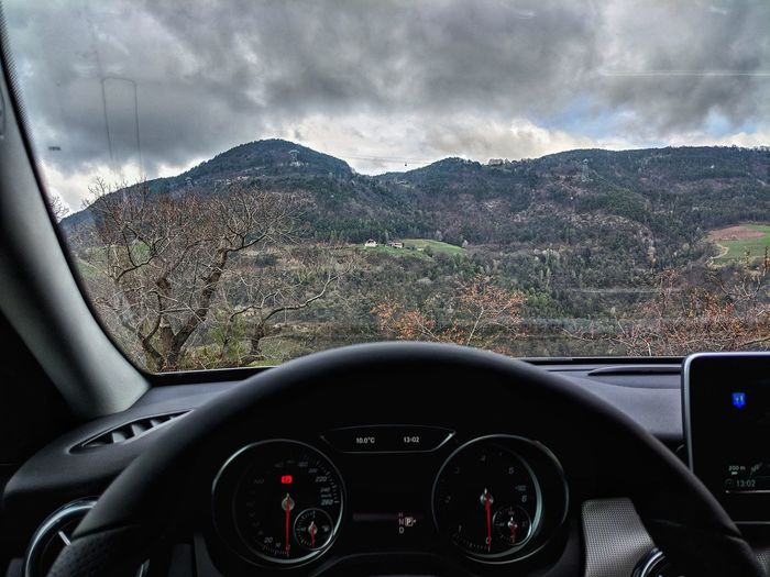 Vintage car against mountains seen through windshield