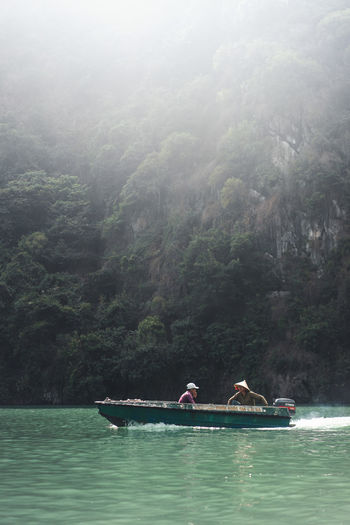 People on boat against mountain