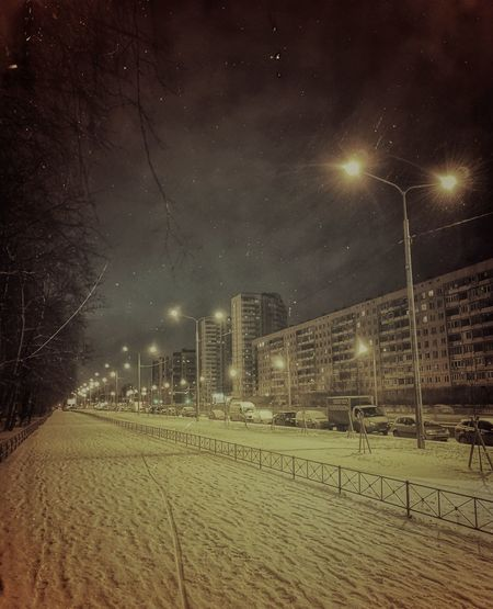 Snow covered street against sky at night