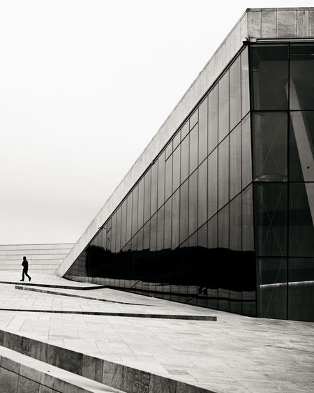 Man walking on modern building against clear sky