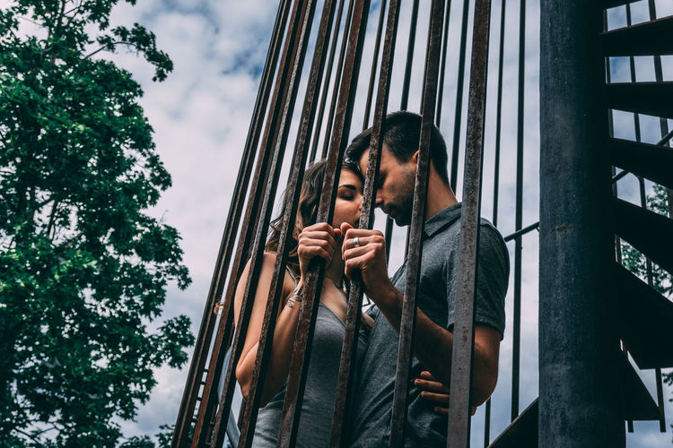 Low angle view of couple standing in the cage
