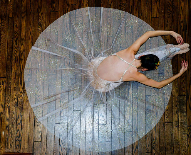High angle view of ballerina wearing dress sitting on hardwood floor