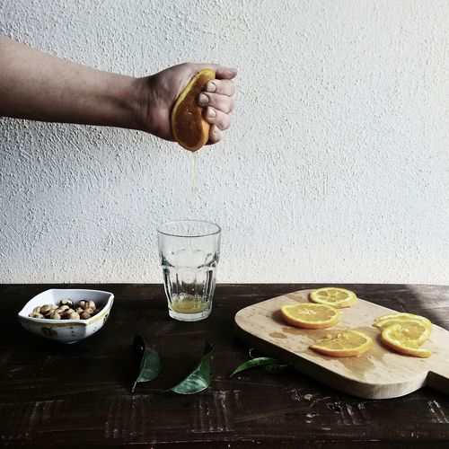 Cropped Image Of Hand Squeezing Sliced Lemon In Fist Against Wall