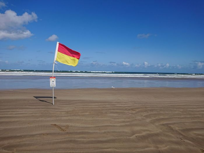 Lifeguards flag pristine beach Flag Ocean Coastline Tourism Blue Sandy Beach Holidays Walks Flags In The Wind  Water Sea Beach Sand Wave Summer Multi Colored Blue Sky Horizon Over Water Lifeguard  Tide Surfing