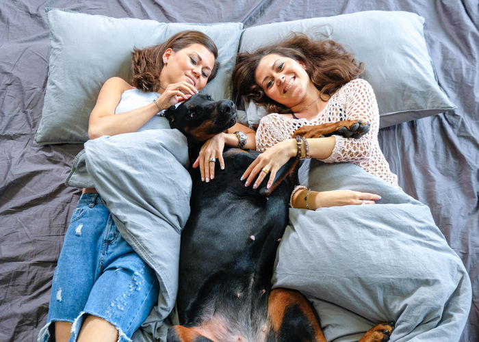 Smiling women with dog lying on bed