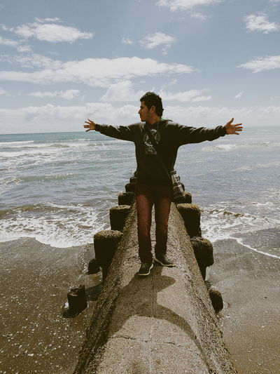 Full length of man with arms outstretched while standing on groyne