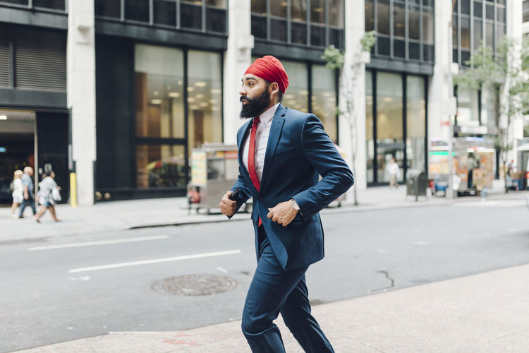 Full length of a man walking on street in city