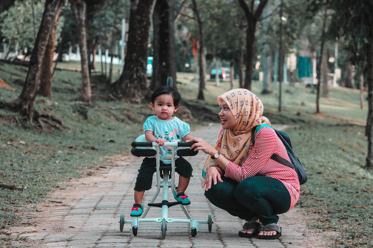 Smiling woman with daughter on toy scooter playing in park
