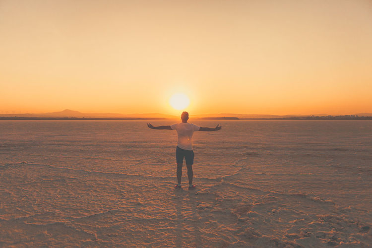 Rear view of man with arms outstretched standing at salt flat against sky during sunset