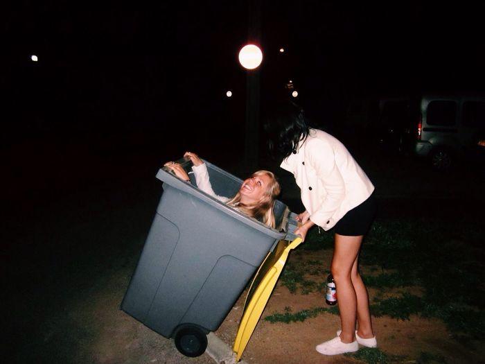Women playing with recycling bin