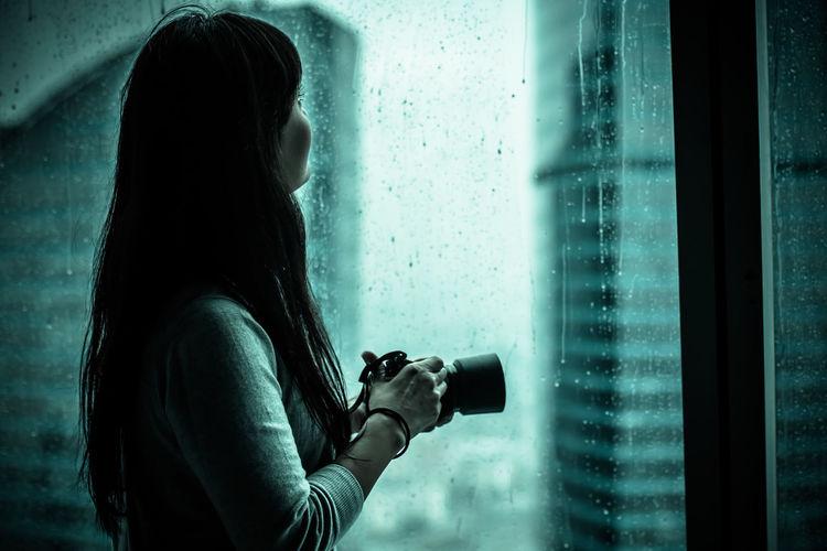 Woman by wet window