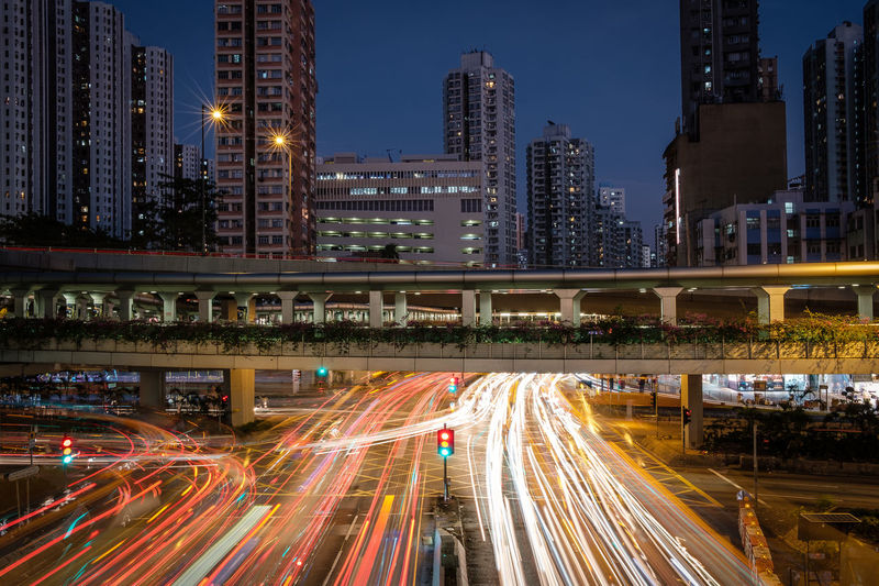 Light Trails On Road By Illuminated Buildings In City At Night
