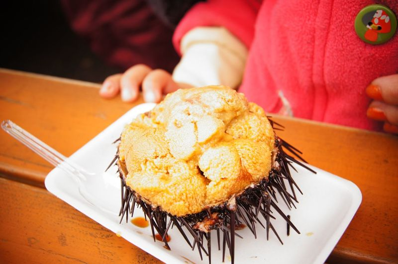Midsection Of Child Having Muffin In Restaurant