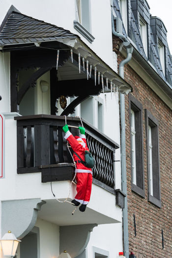 Christmas decoration with fir branches a windowsill outside. Architecture Bird Building Building Exterior Built Structure Chirstmas Decorations Christmas Christmas Tree Day Flag No People Outdoors Patriotism Red Window Window Decorations Windows
