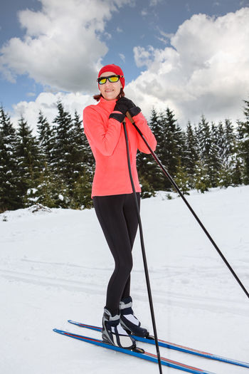 A woman cross-country skiing in the Alps Action, Activity, Adult, Competition, Cross-country, Female, Fit, Fitness, Forest, Healthy, Holidays, Langlauf, Lifestyles, Nordic, People, Running, Skating, Skiing, Snow, Sports, Style, Training, Winter, Woman Clothing Cloud - Sky Cold Temperature Day Full Length Leisure Activity Lifestyles One Person Outdoors Real People Sky Snow Sport Standing Tree Warm Clothing Winter Winter Sport Young Adult