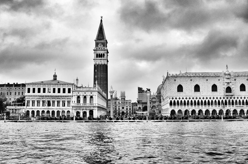 Grand canal by san marco campanile against cloudy sky