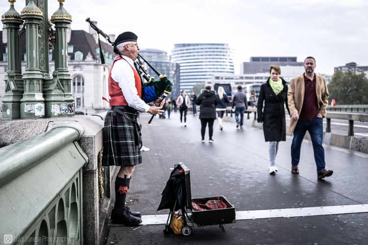 Bagpipe player busking on a bridge in London, as people walk passing by. Human Connection City Outdoors Streetphotography Day Street Full Length Adult Tourist Walking Bagpipes Scottish Bagpiper Tourist Attraction  Busker Street Busking